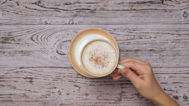 Hand nimmt eine tasse kaffee vom holztisch