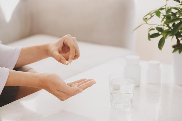 Hand nimmt gelbe kapseln von omega 3, weiße pillen von glucosamin und kalzium auf plastikbox, glas mit wasser am holztisch, draufsicht.