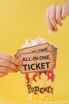 Hand nimmt kinokarten und popcorn von einer papierschale auf einem gelb. frau isst popcorn. kino . flach liegen. copyspace