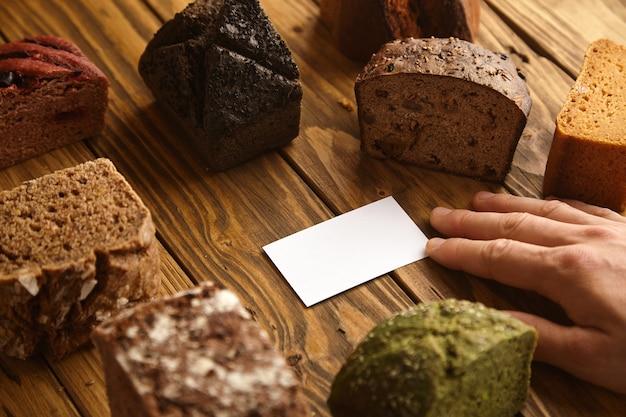 Hand nimmt leere visitenkarte des professionellen handwerklichen bäckers präsentiert in der mitte vieler gemischter alternativer gebackener exotischer brotproben über rustikalem holztisch