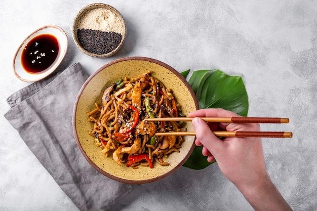 Hand nimmt stäbchen asiatische buchweizen-soba-nudeln mit gemüse, pilzen und hühnchen