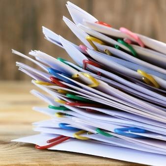 Hand nimmt stapel von dokumenten mit binderclips holztisch, nahaufnahme