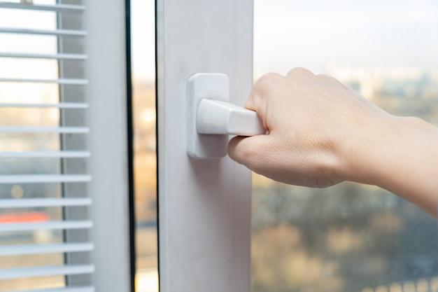 Hand öffnet ein plastikfenster, um den raum für frische luft im frühling und sommer, sonniger tag zu lüften