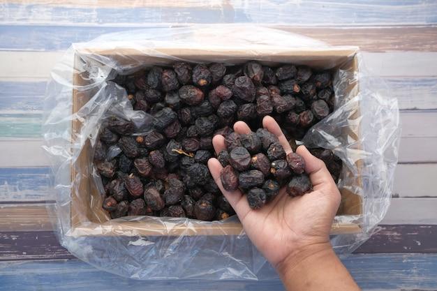 Hand pflücken dattelfrucht aus einer kastenoberansicht