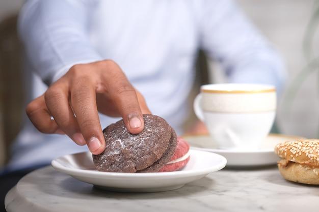 Hand pflücken kekse und tee auf dem tisch,