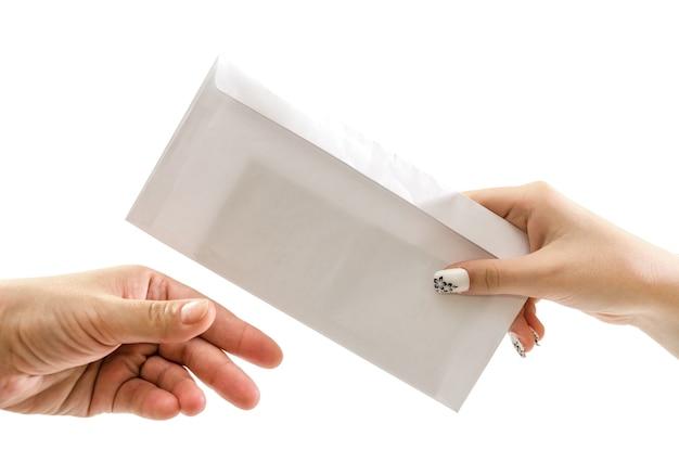 Hand reicht einen umschlag mit geld auf einer weißen oberfläche