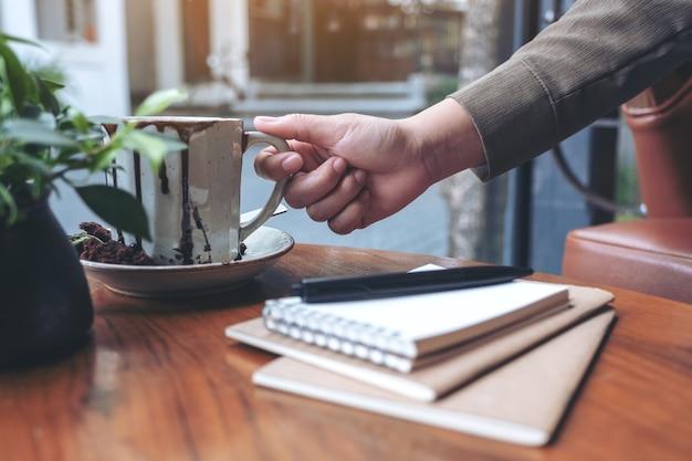 Hand schnappte sich eine tasse heißen kaffee mit notizbüchern auf holztisch