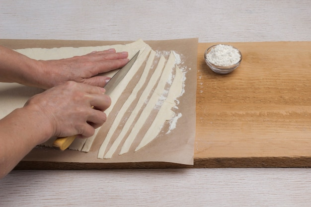 Hand schneidet gerollten teig mit einem messer in streifen. prozess der herstellung von nudeln