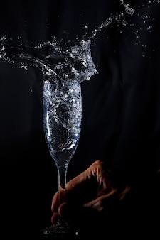 Hand schüttelt ein glas mit wasser