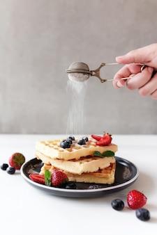 Hand schüttelt puderzucker über stapel waffeln auf einem teller auf dem tisch mit blaubeeren, gehackten erdbeeren und minzblättern. foto in hoher qualität