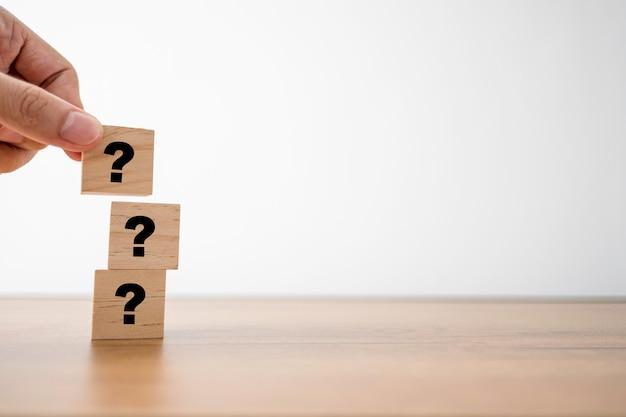 Hand setzen fragezeichen auf holzwürfel für fragen und antworten oder frage und antwort