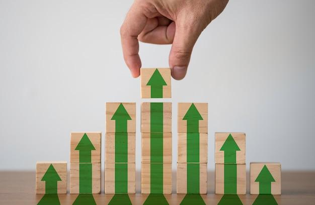 Hand setzen holzwürfel block, die bildschirm erhöhen oder grünen pfeil nach oben drucken.