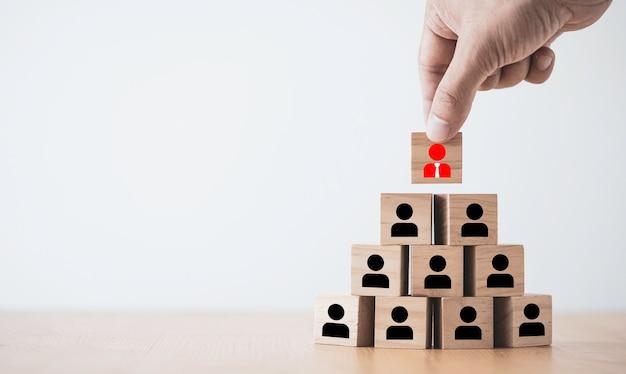 Hand setzen manager symbol auf mitarbeiter mitarbeiter, die bildschirm auf holzblock drucken.