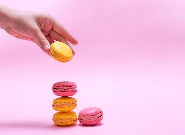 Hand setzt makronen in spalte auf rosa hintergrund