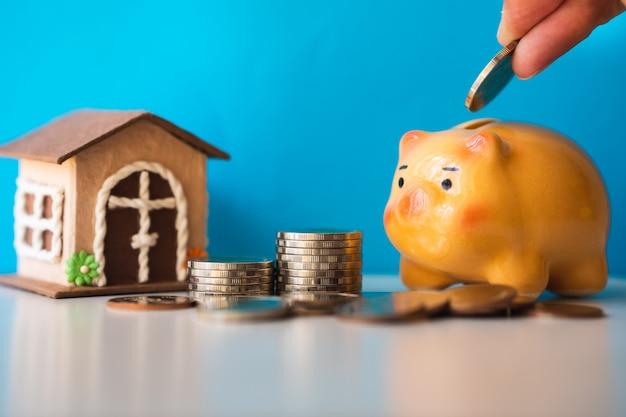 Hand setzte münze zum sparschwein auf blauem hintergrund unter verwendung als geldsparendes eigentumskonzept