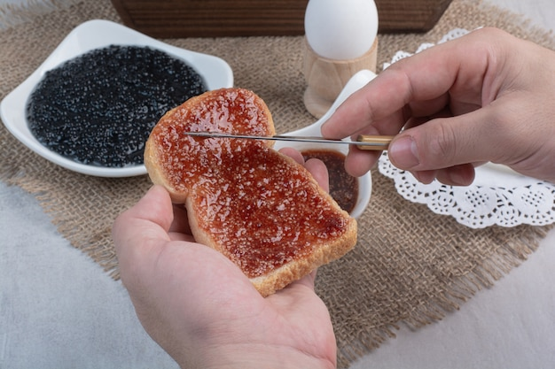 Hand slathers marmelade auf brot mit messer.