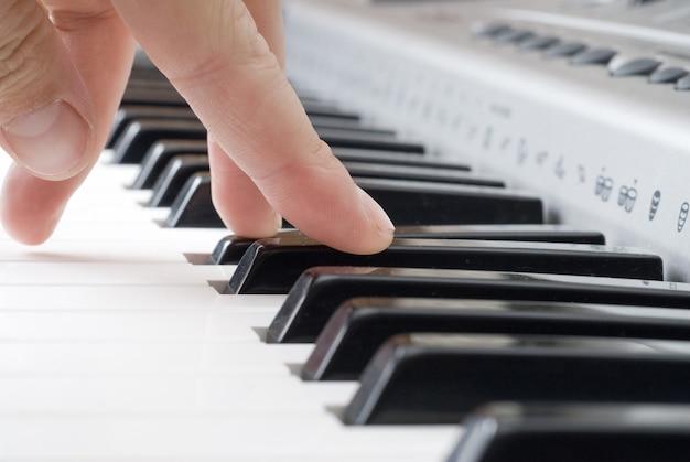 Hand spielt musik auf dem klavier