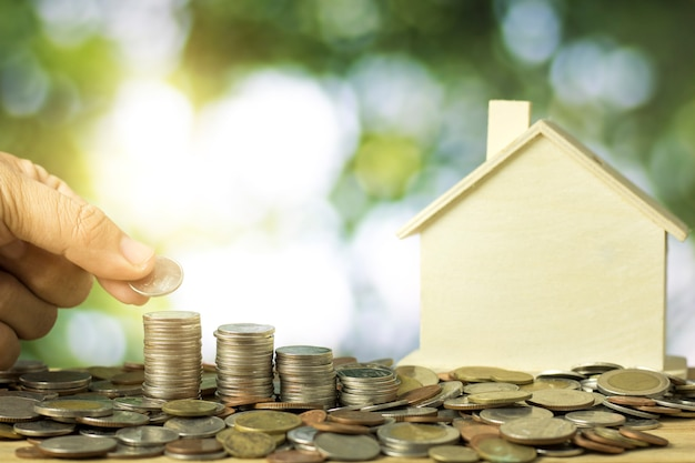 Hand stapelten geldmünzen mit musterhaus, immobilienkonzept