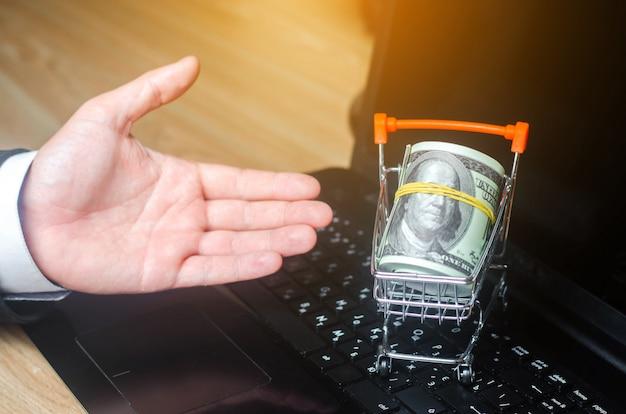 Hand stellt einen supermarktwagen auf einem laptop dar. das konzept des online-einkaufs.