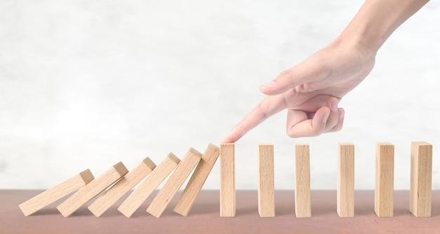 Hand stoppt den domino-effekt durch einmaliges stoppen