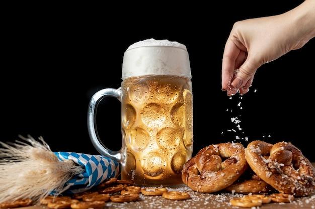 Hand streuen salz auf bayerischen snacks