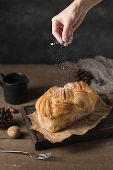 Hand streuen zucker auf hausgemachten kuchen