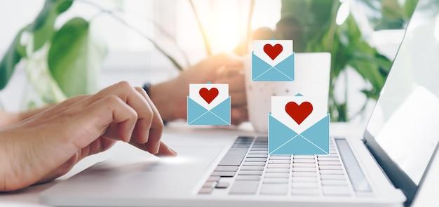 Hand tippt tastatur mit laptop-computer mit social-media-liebesbrief-mail senden symbole valentinstag konzept.