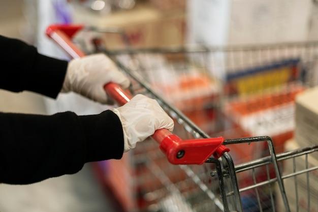 Hand trägt einen latexhandschuh, während sie einen einkaufswagen schieben, um eine kontamination mit coronaviren zu verhindern