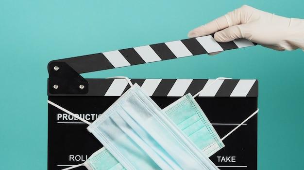 Hand trägt weiße medizinische handschuhe und hält schwarzes clapper board oder filmschiefer mit gesichtsmaske. es verwendet in film, filmproduktion und kinoindustrie auf grünem oder tiffany blue hintergrund.
