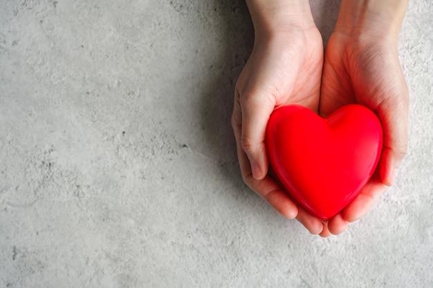 Hand tragen herz. liebe und cardio gesundheit konzept. valentinstag und hochzeitsthema.