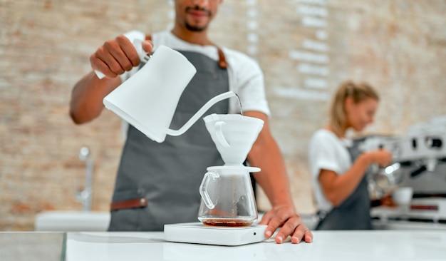 Hand-tropfkaffee, barista macht tropfkaffee. barista kocht kaffee, methode übergießen, kaffee abtropfen lassen.