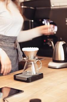 Hand tropft kaffee, barista gießt wasser auf kaffeesatz mit filter