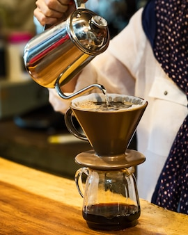 Hand tropft kaffee, barista gießt wasser auf kaffeesatz mit filter.