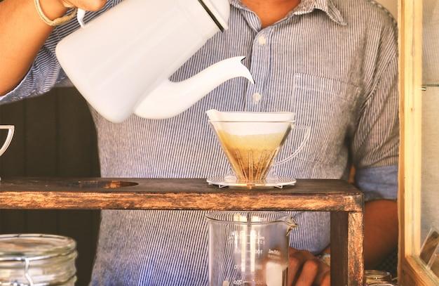 Hand tropft kaffee. gebrühten arabica-kaffee zubereiten