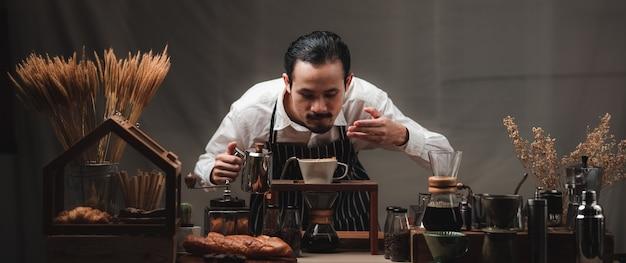 Hand tropft kaffeefilter, barista gießt heißes wasser auf gerösteten kaffeepulver mit filter