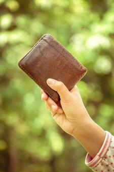 Hand und geldbörse mit retro- weinleseart des filtereffektes