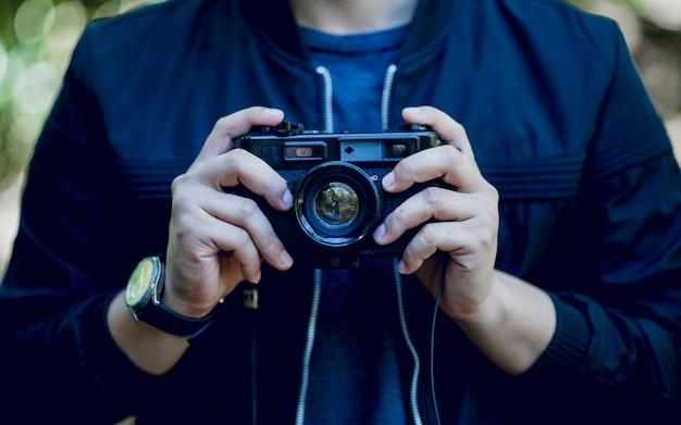 Hand und kamera des fotografen reise in die berge und natur konzeptfotograf