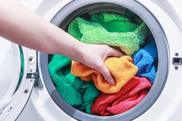 Hand und legt die wäsche in die waschmaschine