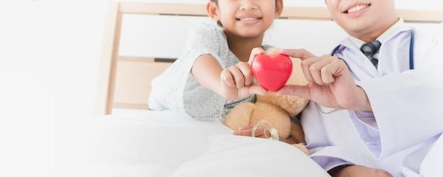 Hand und männlicher doktor des asiatischen kindes halten das rote herz, das auf bett im krankenhaus liegt.