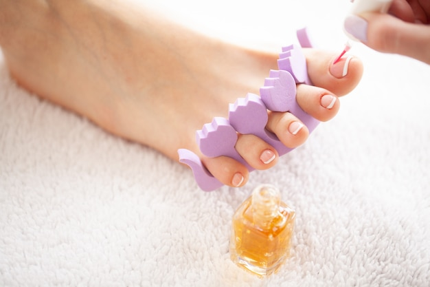 Hand- und nagelpflege. die füße der schönen frauen mit pediküre im schönheitssalon. der meister, der auf nagel aufträgt. spa maniküre