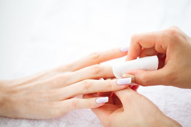Hand- und nagelpflege. schöne frauenhände mit perfekter maniküre. maniküre-meister, der wattepads in den händen hält. schönheitstag. spa maniküre
