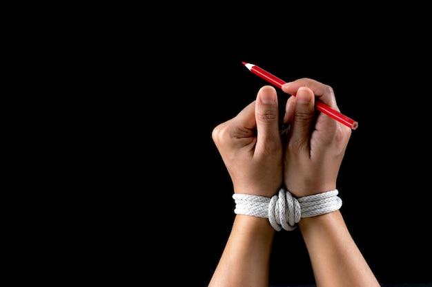 Hand und roter bleistift gebunden mit seil