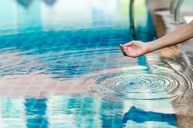 Hand und wasser berühren das blaue wasser. um das konzept des trinkwassers mit textfreiraum aufzufrischen.