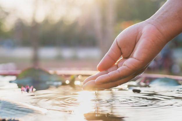 Hand und wasser mit sonnenuntergang
