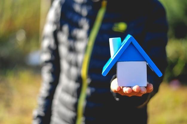 Hand und zuhause des gebäudes baby. und viele menschen träumen davon, ein eigenes zuhause zu haben.