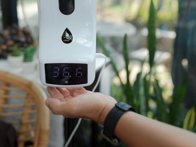 Hand unter temperatur-screening-digitalanzeige normale temperatur mit alkoholgel, messung der körpertemperatur durch auflegen der hand auf den sensor für obligatorische kontrollen der kunden während der covid-19-pandemie