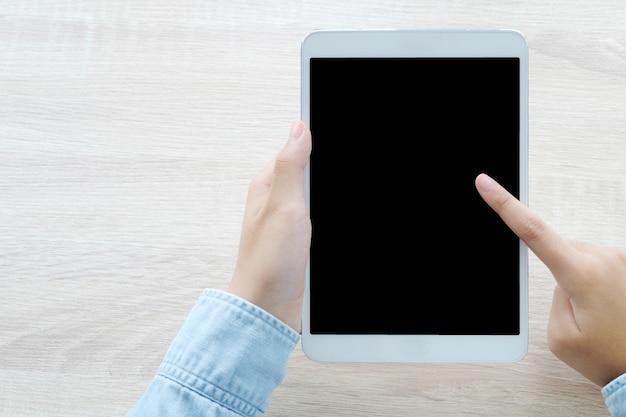 Hand unter verwendung der tablette mit leerem bildschirm für spott oben über tabellenhintergrund