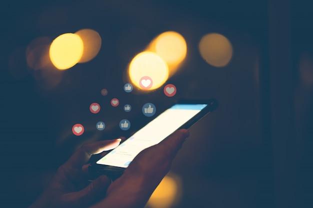 Hand unter verwendung des intelligenten telefons mit social media-konzept.
