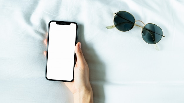Hand unter verwendung des leeren bildschirms des smartphone auf raum, während der freizeit.