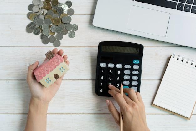 Hand unter verwendung des taschenrechners beim halten des hausmodells, des notizbuchs und des computer-laptops, sparpläne für das finanzielle konzept des wohnraums